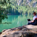 student-sitzt-am-bergsee-ufer-und-lernt-mit-laptop