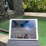 laptop-steht-aufgeklappt-auf-knien-dahinter-pool-und-buddastatue-im-garten